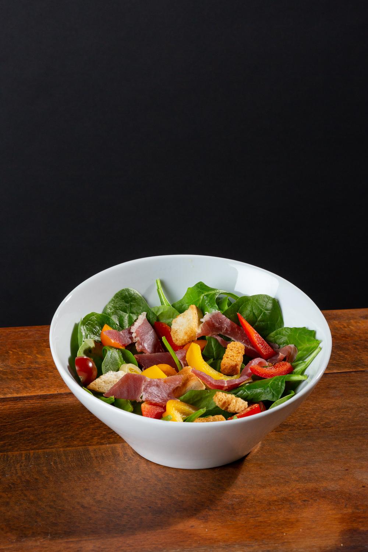 Un grand bol avec de la salade en photo studio avec un fond noir et une table en bois