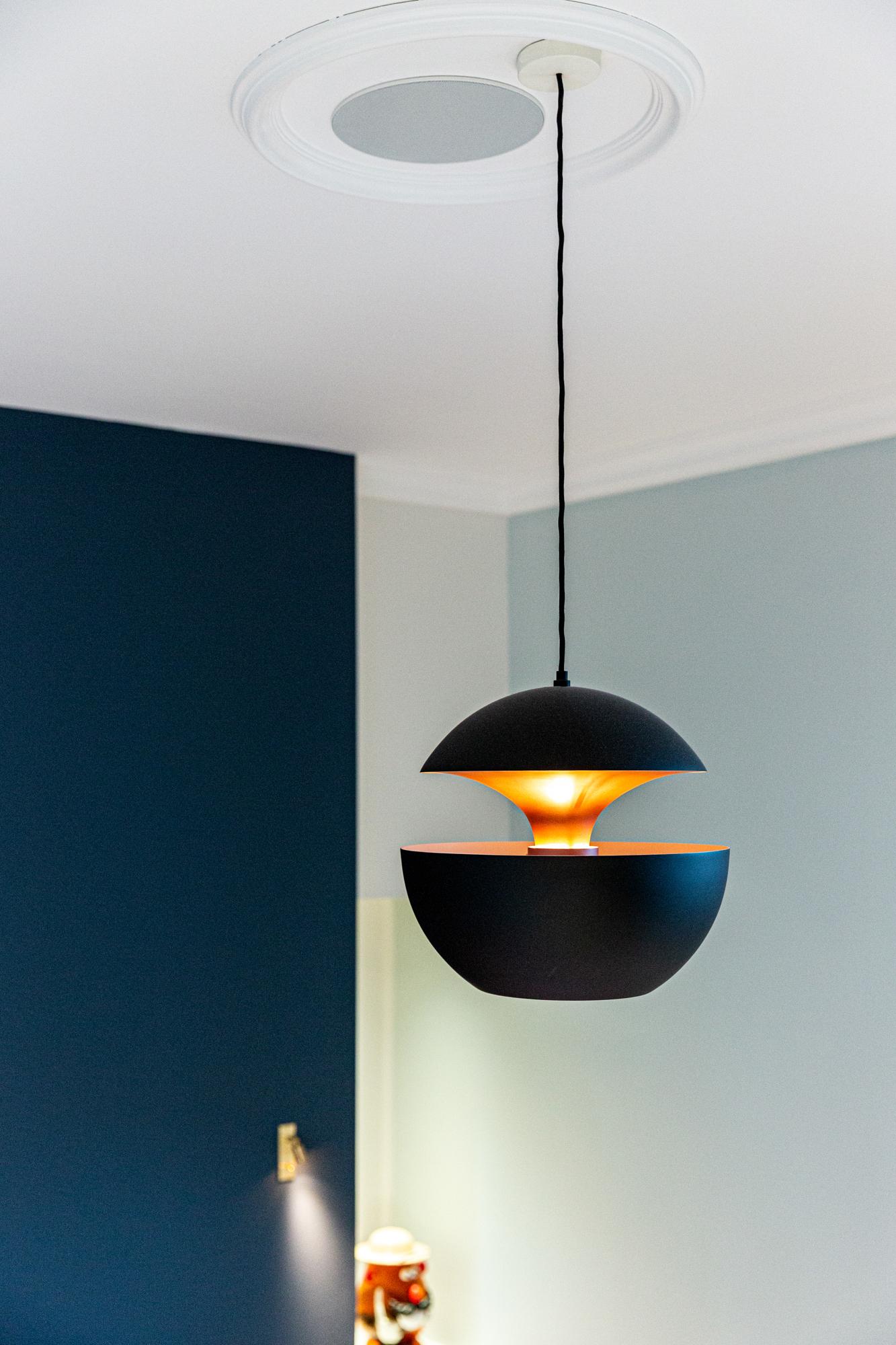 Lampe ronde bleue foncée, dans une chambre. Photographie design et décoration.