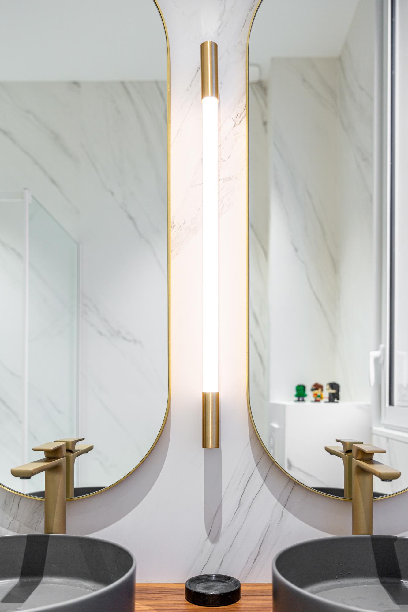 Eclairage de type tube dans une salle de bain avec deux miroirs. On aperçoit deux vasques